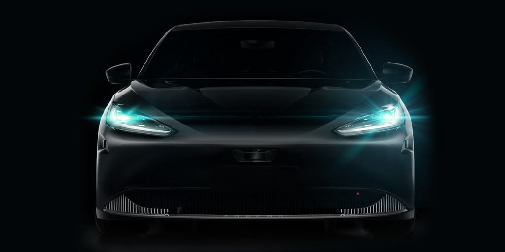 Front of a black sports car with the headlights on
